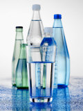 A Glass in Front of Mineral Water Bottles Photographic Print by Alexander Feig