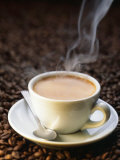 A Steaming Cup of Coffee on Coffee Beans Fotografie-Druck von Peter Sapper