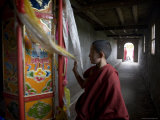 Young Monk Spinning a Prayer Wheel with Flags in a Monastery, Qinghai, China Fotografisk tryk af David Evans