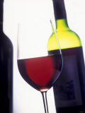 A Glass of Red Wine with a Bottle in the Background Photographic Print by Armin Faber