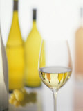 A Glass of White Wine and Wine Bottles in Background Photographic Print by Ulrike Koeb