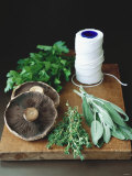 Mushrooms, Fresh Herbs & Kitchen String on Chopping Board Photographic Print by Michael Paul