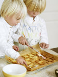 Two Children Brushing Biscuits with Glace Icing Photographic Print by Renate Forster