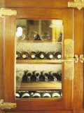Several Wine Bottles in Wood-Panelled Drinks Cabinet Photographic Print by Peter Medilek