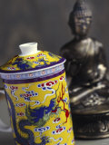 Decorated Teacup with Lid in Front of Statue of Buddha Photographic Print by Dr. Martin Baumgärtner