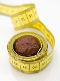 Chocolate Truffle Lying in Rolled-Up Tape Measure Photographic Print by Elisabeth Cölfen