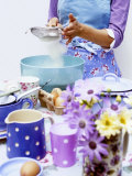 Woman Sieving Flour into a Bowl, Crockery & Eggs in Front Photographic Print by Linda Burgess