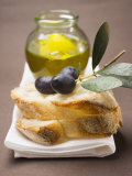 Olive Sprig with Black Olives on White Bread, Olive Oil Behind Lámina fotográfica