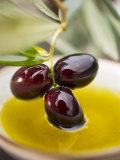 Dipping Olive Sprig with Black Olives in Olive Oil Lámina fotográfica