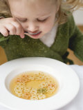 Small Girl Eating Soup with Teddy Bear Pasta Photographic Print