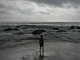 Child Standing at the Edge of Tide Photographie par Krzysztof Rost