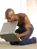 African-American Man Biting Laptop on the Floor Photographic Print by Jim McGuire