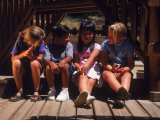 Children Sitting in Playground Photographic Print by Mark Gibson