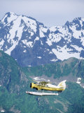 Seaplane in Flight Near Mountains, AK Photographic Print by Jim Oltersdorf
