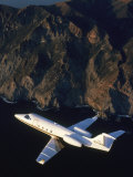 Lear Jet in Flight Over Mountains Fotografie-Druck von Garry Adams