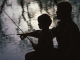 Silhouette of Father and Five-year-old Son Fishing Photographic Print by Kevin Beebe