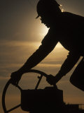 Silhouette of Oil and Gas Worker Turning Valve Photographic Print by Kevin Beebe