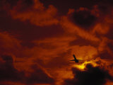 Silhouette of Airplane in Flight at Sunset Photographic Print by Roger Holden