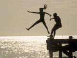 Silhouette of Girls Jumping off Pier Photographic Print by Anne Flinn Powell