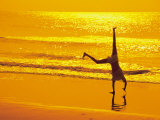 Girl Doing Cartwheels on Beach at Sunset Photographic Print by Jennifer Broadus