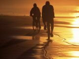 Couple Biking Toward Sunset, Monterey, CA Photographic Print by Hal Gage