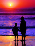 Sunset Silhouette of Mom and Boy Along Coast Photographic Print by Russell Burden