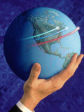 Businessman's Hand Holding Globe Photographic Print by Guy Crittenden