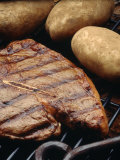 Steak and Potato on Grill Photographic Print by Howard Sokol