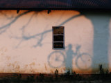 Shadow on a Wall of a Man Holding a Bicycle Photographic Print by Chris Johns
