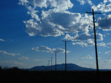 Silhouetted Telephone Poles under Puffy Clouds Photographic Print by Raymond Gehman
