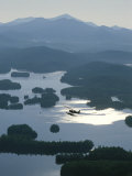 A Floatplane Flies over Long Lake with Mount Marcy in the Background Photographic Print by James P. Blair