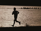 Silhouette of a Jogger Next to Water Photographic Print by Roy Gumpel