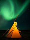 A Solitary Tepee is Illuminated by the Aurora Borealis Photographic Print by Raymond Gehman