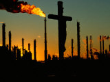 A Crucifix is Silhouetted against Refinery Stacks Lámina fotográfica por Kittner, Sam