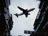 A Jet Soars Above the Crowded Streets of Hong Kong Photographic Print by Jodi Cobb