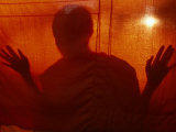 A Buddhist Monk is Silhouetted Behind a Hanging Curtain Photographie par Paul Chesley