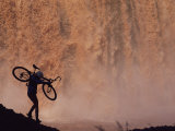 Silhouetted Cyclist Carrying Cycle Past Falls Photographic Print by Bill Hatcher
