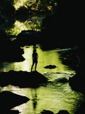 A Woman is Silhouetted Standing on a Rock Jutting out from a Stream Photographic Print by Barry Tessman