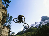 Man Jumping on His Mountain Bike with Ha Ling Peak in the Background Impressão fotográfica por Mark Cosslett