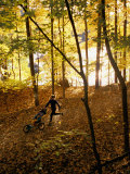 A Woman Pushes a Baby Stroller as She Jogs Through a Wooded Area Photographic Print by Skip Brown