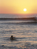 A Woman Paddles out to Sea for Sunset Surfing Stampa fotografica di Chin, Jimmy