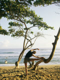 A Woman Stretches Her Body on a Small Tree at a Sandy Beach Photographic Print by Skip Brown