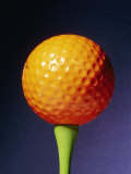 An Orange Golf Ball on a Green Tee with a Blue Background Photographic Print by Brian Gordon Green