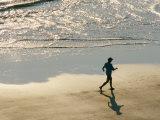 A Jogger Runs Along the Beach Photographic Print by Joel Sartore