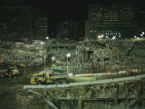 An Elevated View of Ground Zeros Devastation at Night; Crews, Their Vehicles, and Other Equipment Photographie par Ira Block