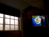 Stormy View outside Window with Television Displaying a Hurricane Watch Photographic Print by Raul Touzon