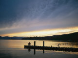A Fisherman at Dawn Tries His Luck from the End of a Pier Photographic Print by Michael S. Lewis