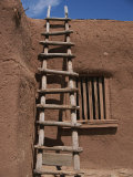 A Handmade Wooden Ladder Rests against an Adobe Structure Photographic Print by Stacy Gold