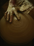 Close-up of the Brown Muddy Hand of a Potter as He Spins a Clay Pot on His Wheel Photographic Print by Thomas J. Abercrombie