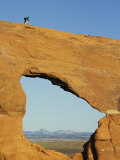 Brad Richman Rides his Bicycle over Hole in the Rock Formation Photographic Print by Bill Hatcher
